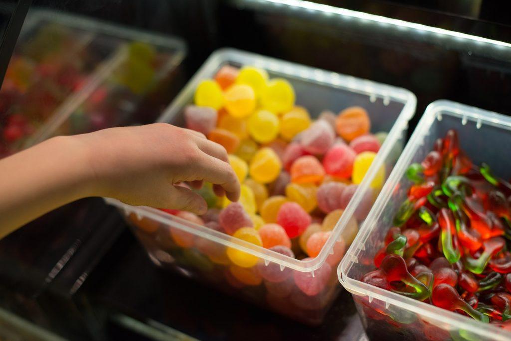 Criança cercada de doces. Dúvida comum: crianças pequenas podem consumir adoçantes? É proibido?