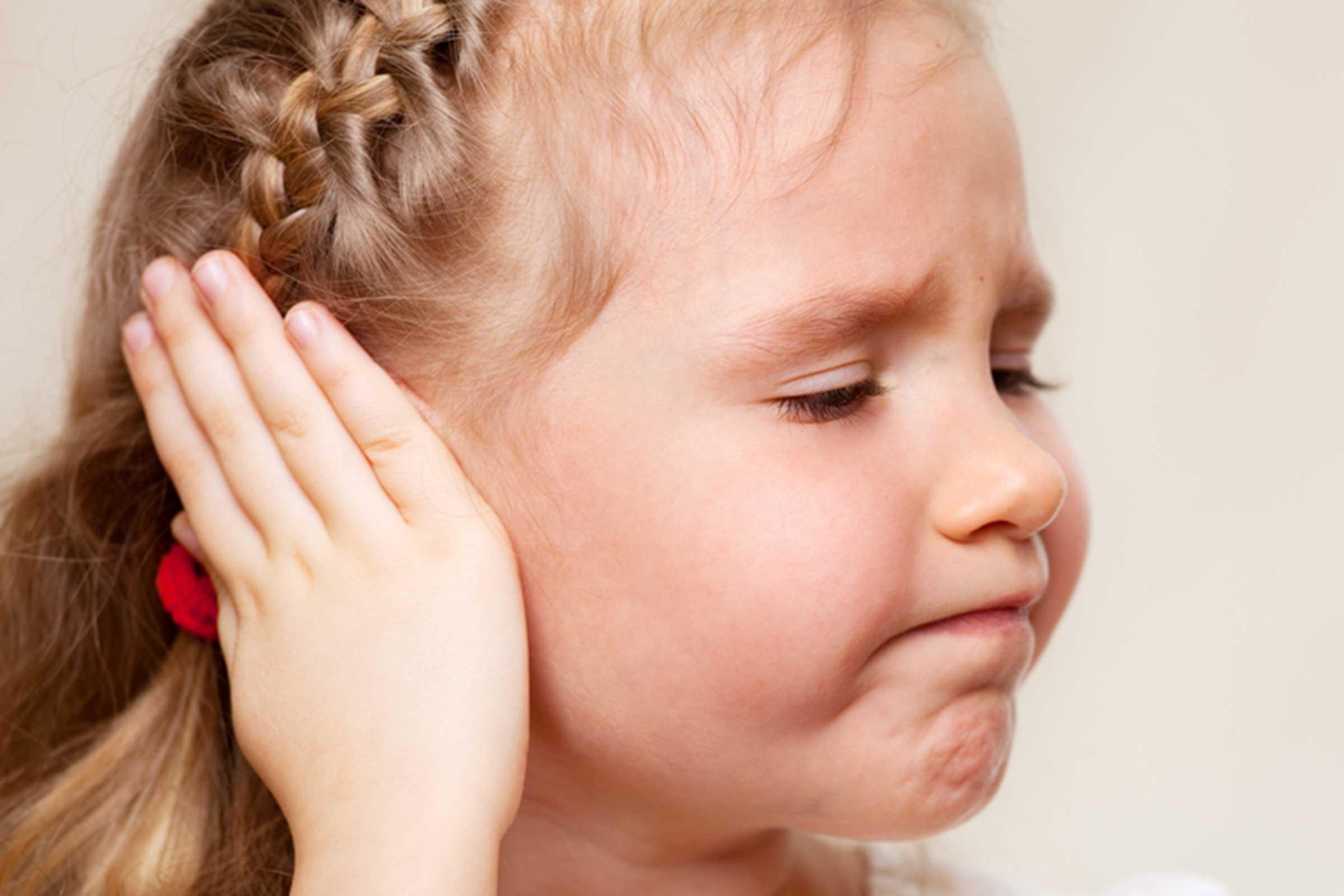 Criança com dor de ouvido coloca a mão na orelha