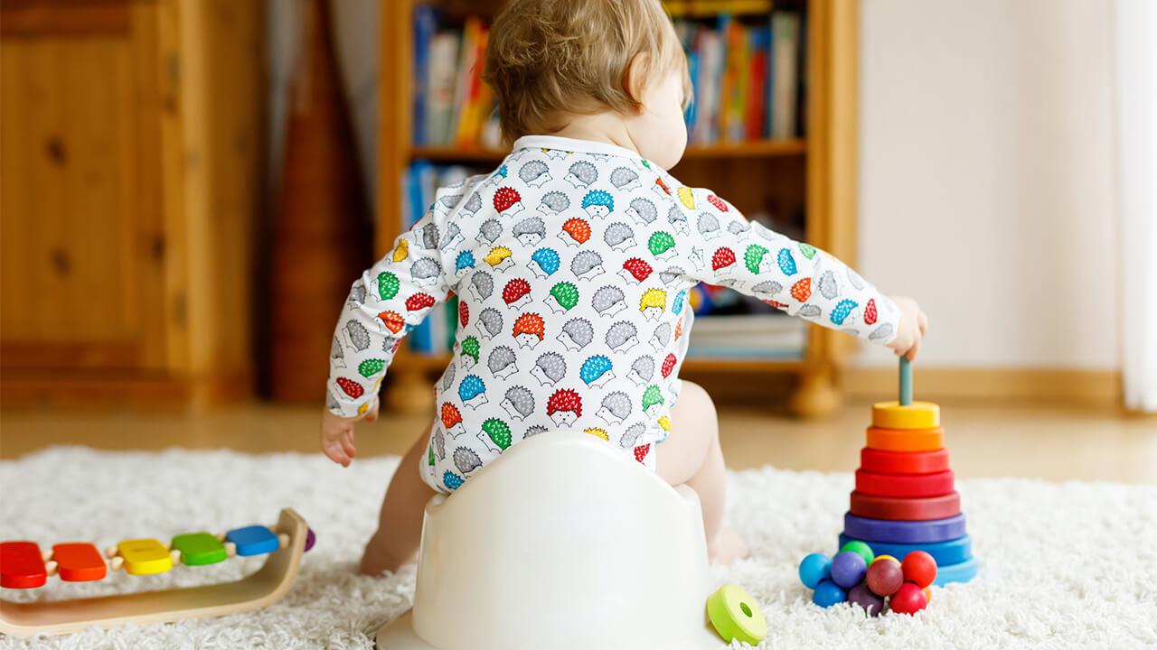 Criança brinca ao usar penico e fazer suas necessidades