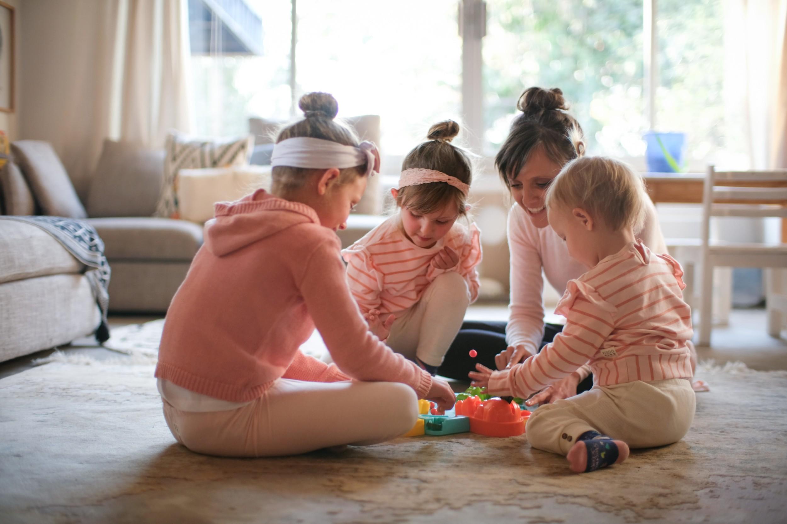 Mãe interage com as crianças ao brincar na sala de casa