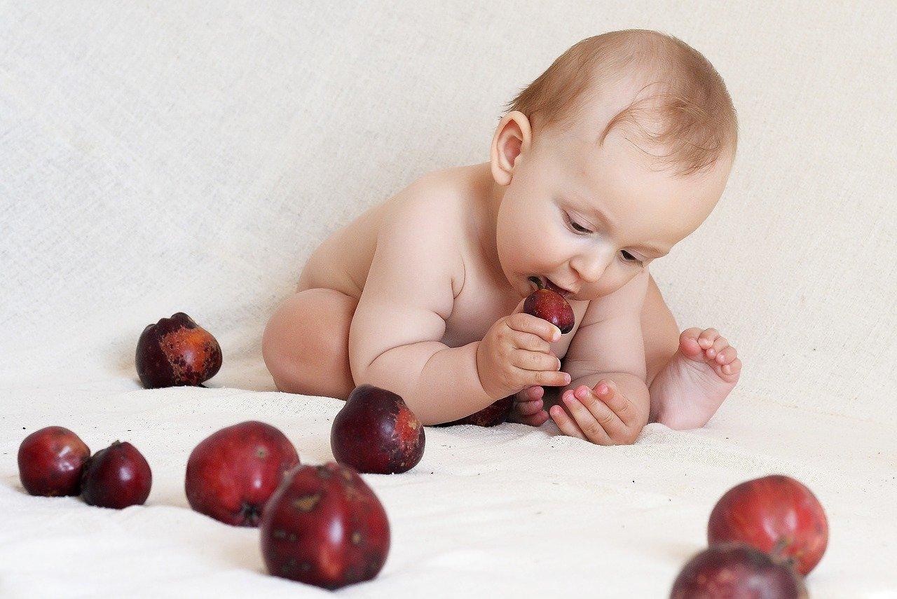 Bebê cercado de frutas: alimentação saudável depende dos pais