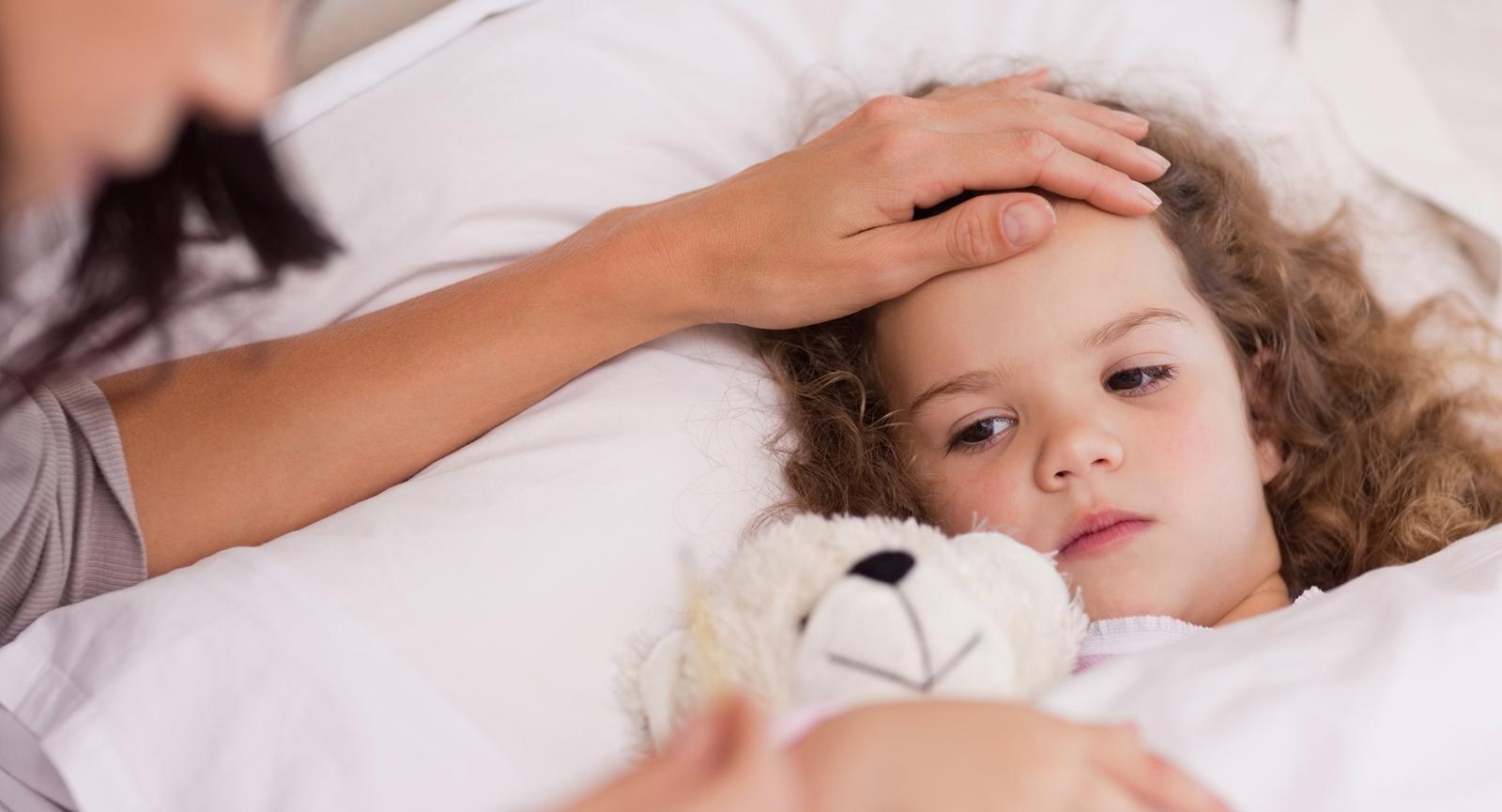 Criança com pneumonia é consolada pela mãe