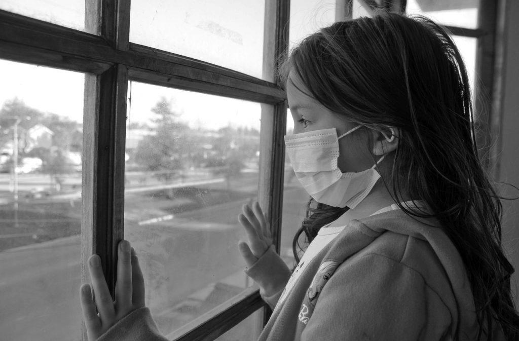 Criança protegida com máscara olha pela janela: pediatras devem estar atentos a todos os sinais da criança enferma