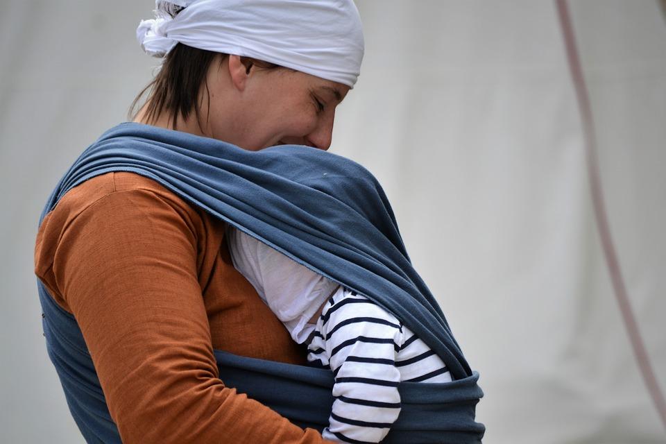 Bebê é carregado por sua mãe usando um sling: uso do equipamento assegura que os pais desviem de ruas esburacadas