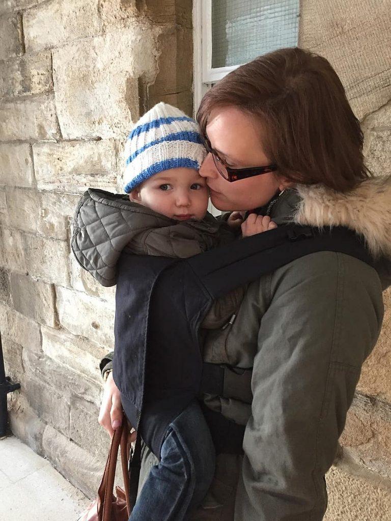 Mulher carrega seu filho usando o sling: benefícios são inúmeros, inclusive evitam as cólicas do bebê.
