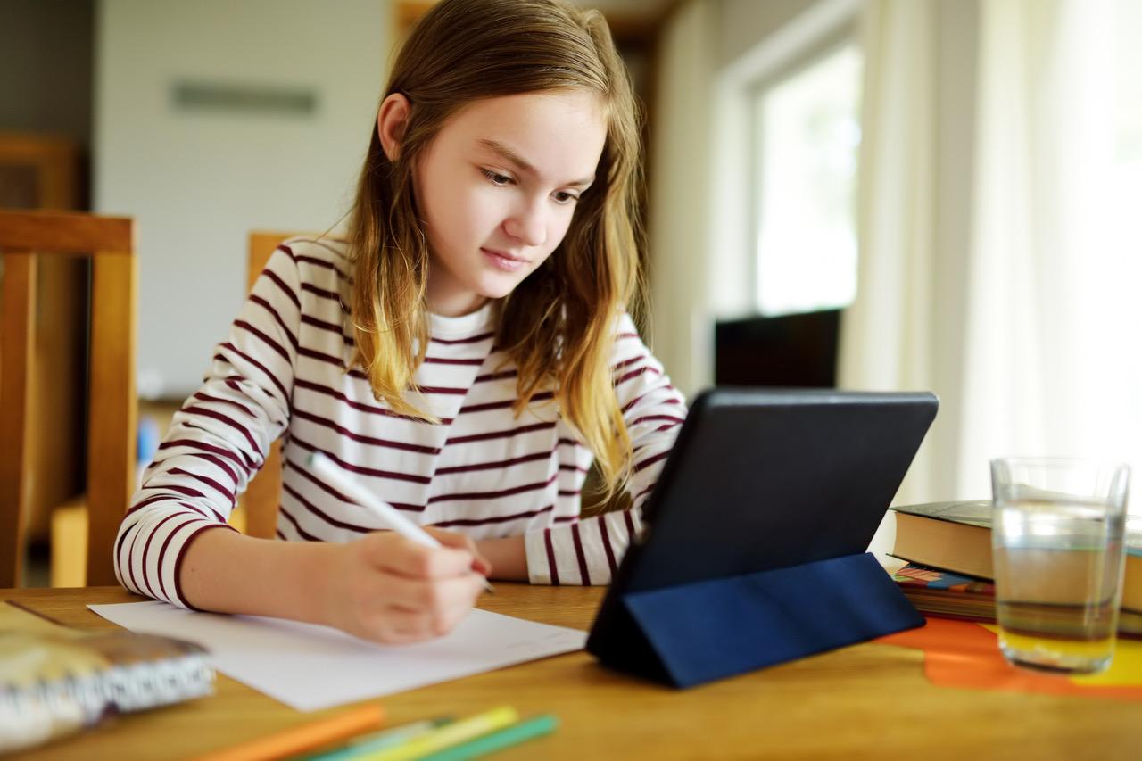 Menina realiza tarefa escolar olhando para um tablet: saiba como ajudar no aprendizado online das crianças