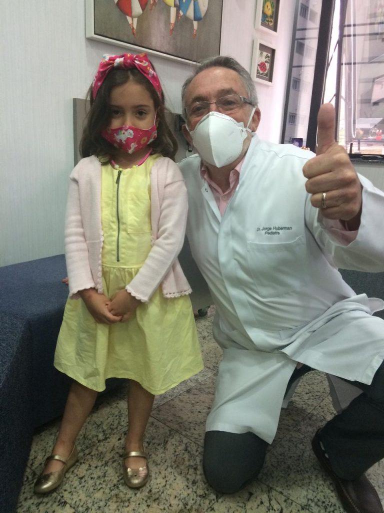 """O pediatra Jorge Huberman ao lado da paciente, Laura: """"é importante garantir que as crianças não voltem às aulas todas de uma vez""""."""
