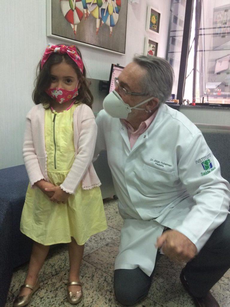 """O pediatra Jorge Huberman usa máscara ao lado da paciente Laura: """"as máscaras perdem muito da sua eficiência por não se ajustarem ao rosto das crianças"""