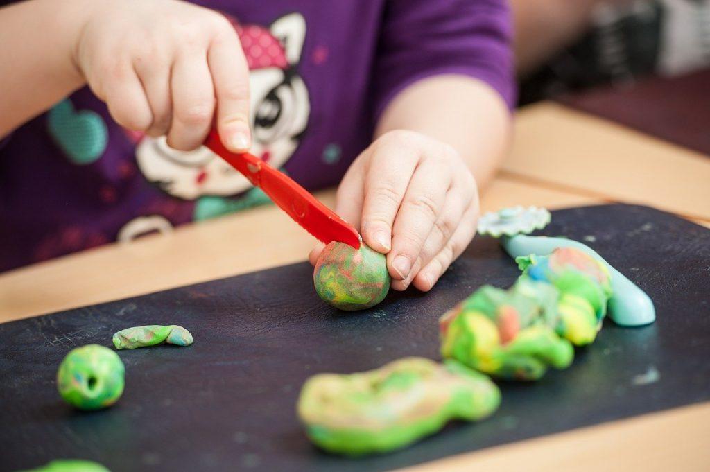 Criança brinca com massinha: excelente atividade para distrair os pequenos