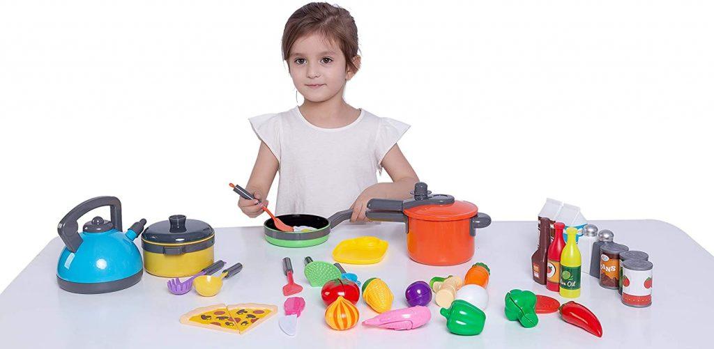 Menina simula cozinhar com objetos falsos de cozinha: potes plásticos podem ser usados nas brincadeiras das crianças.