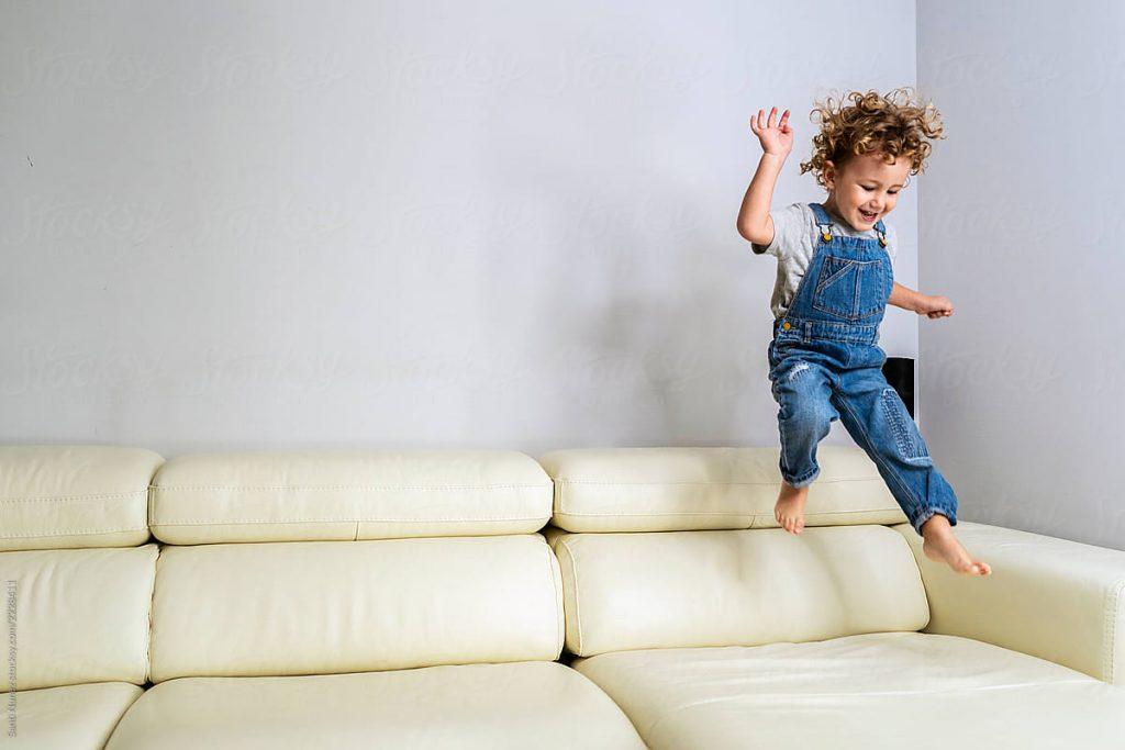 Criança brinca de pular no sofá: tomando todos os cuidados e tendo a supervisão de um adulto, brincadeira também pode ser uma boa saída para espantar o tédio.