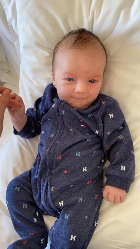 O paciente Henry deitado em seu berço: quando a criança abre a mão já mostra sinal de desenvolvimento