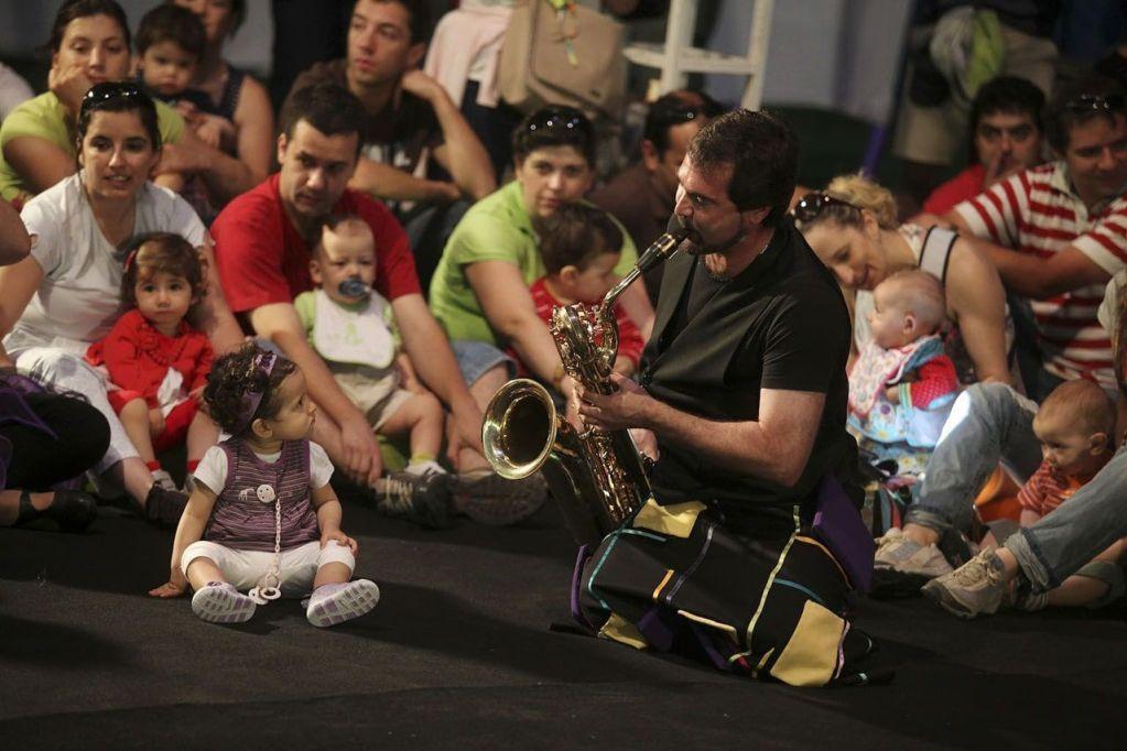 A trilha sonora ideal do meu bebê: músico é observado por diversos bebês durante apresentação.
