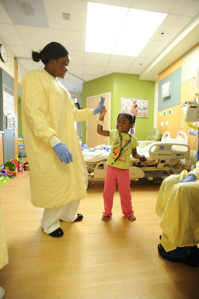 Criança cumprimenta profissional da saúde em hospital: clínica médica no Rio de Janeiro permite a visita de crianças