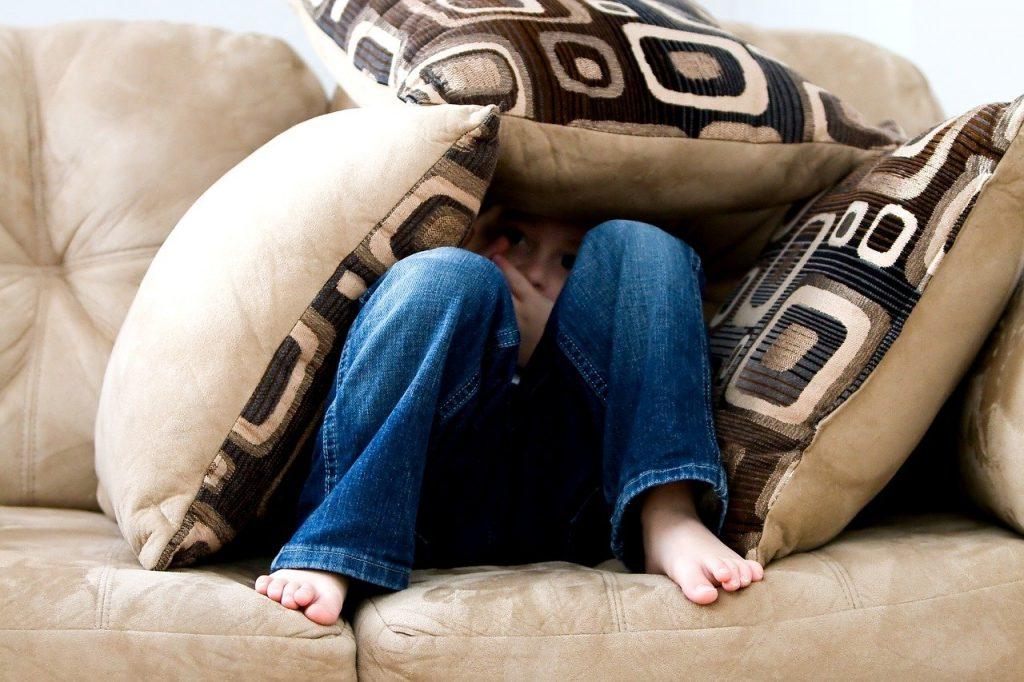 Criança é vista entre almofadas: hora da criança dormir é muito complicada