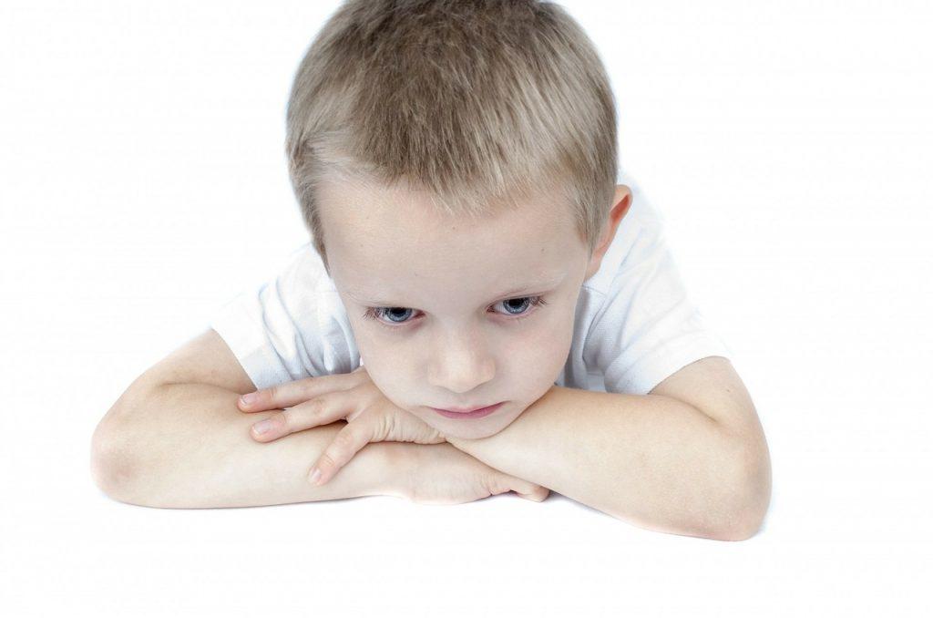 Criança aparenta tristeza; pesquisa revela: crianças que são vítimas de abusos verbais têm mais problemas de comportamento