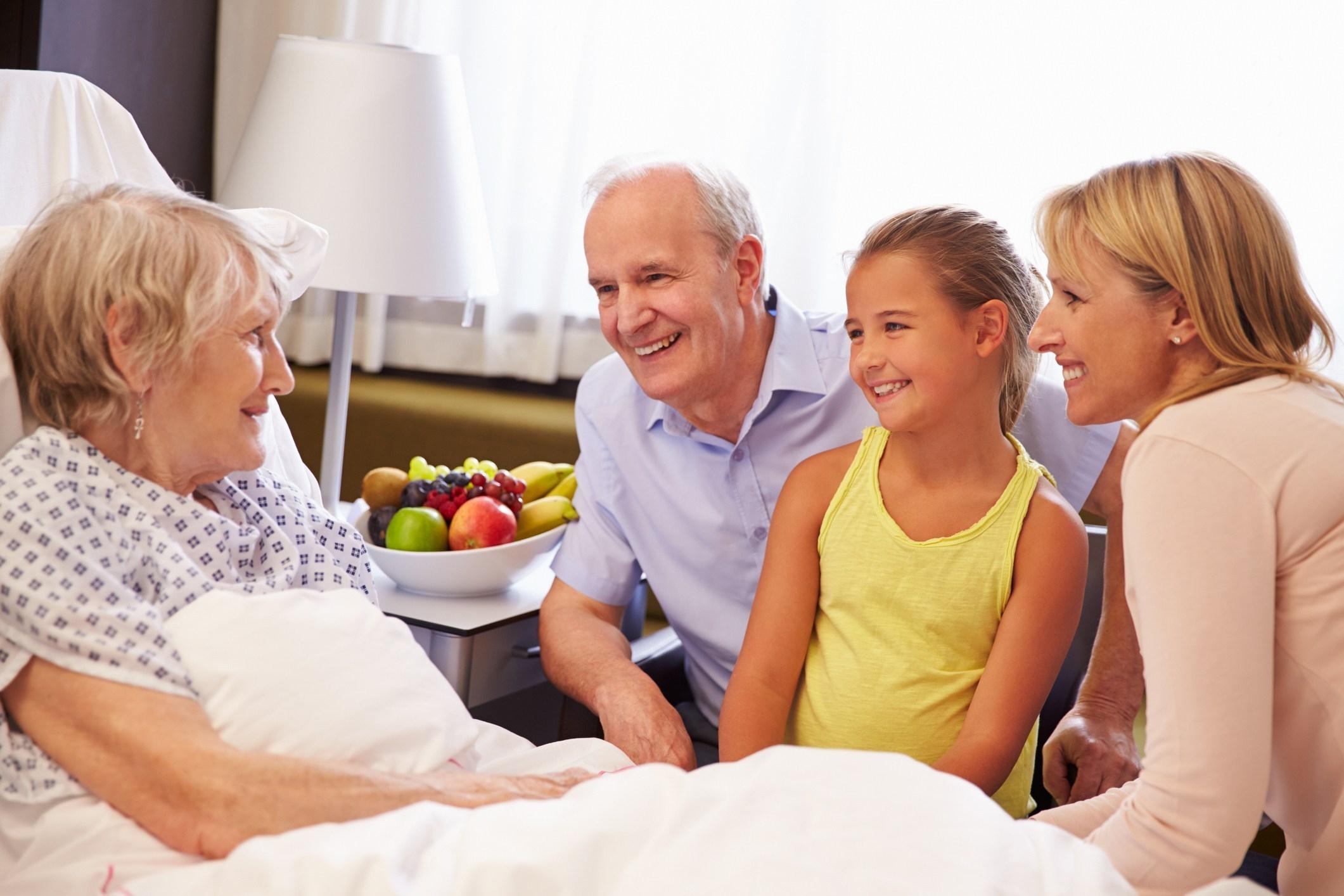 Menina ao lado de adultos visita idosa em hospital: projeto regula visita de crianças a hospital