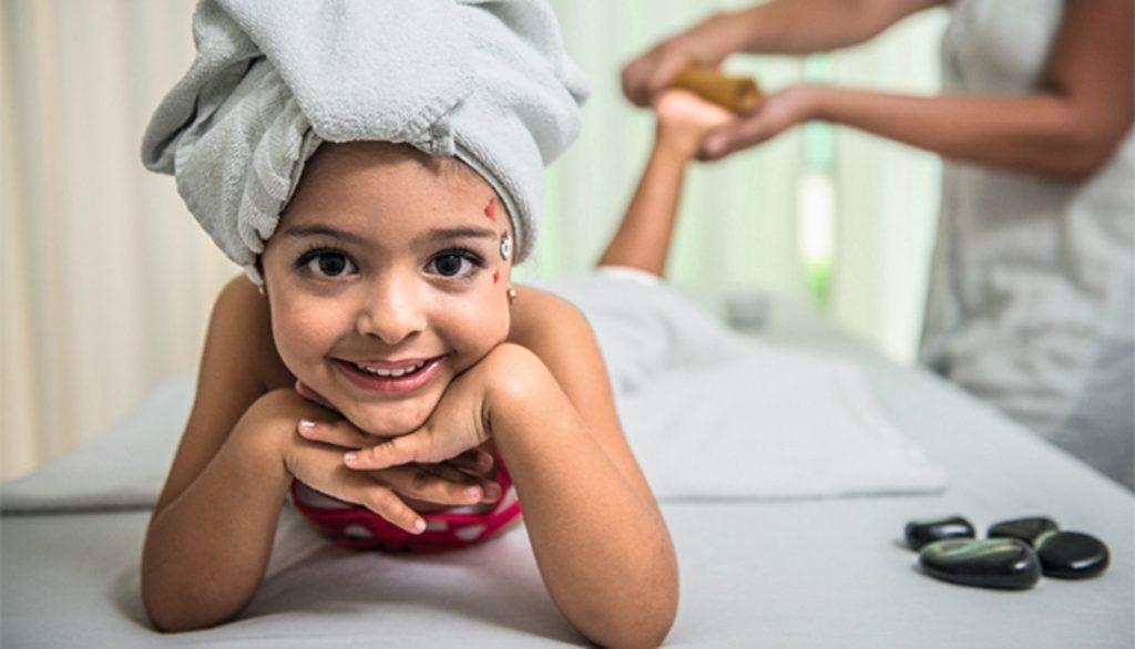 Dor do crescimento: criança sorri ao receber massagem