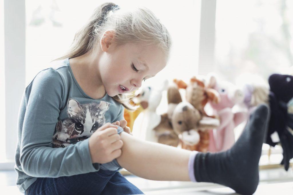 Menina observa a sua perna: artrite idiopática juvenil precisa de atenção especial do médico