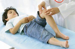 Menino tem seu joelho examinado por médico: as queixas de dores em membros são bastante comuns em crianças