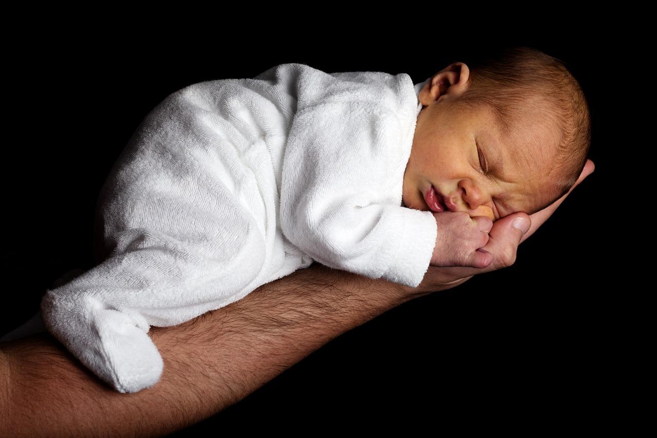 Bebê prematuro dorme no braço de um adulto; um momento que sempre gera tensão nos pais, após vários dias de internação e preocupação no hospital é; a alta do bebê prematuro: e agora?