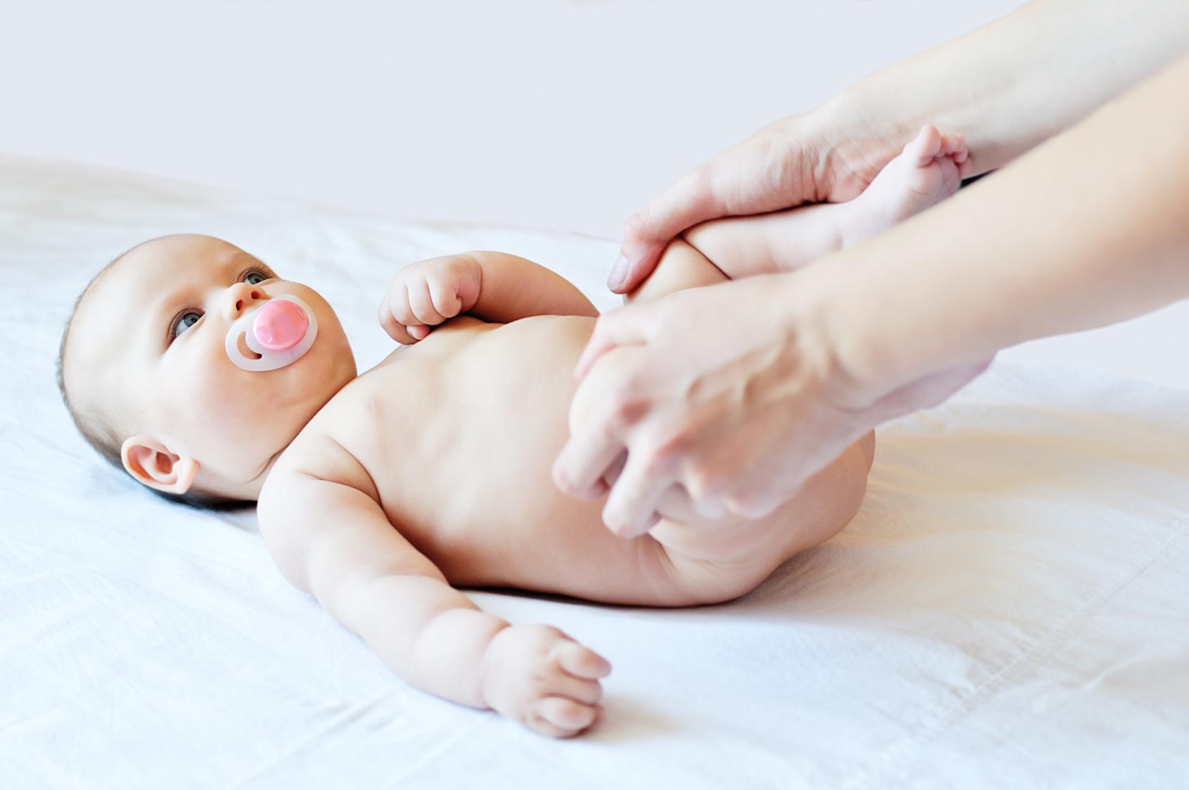 Adulto ajeita pernas de bebê com DDQ displasia de desenvolvimento do quadril