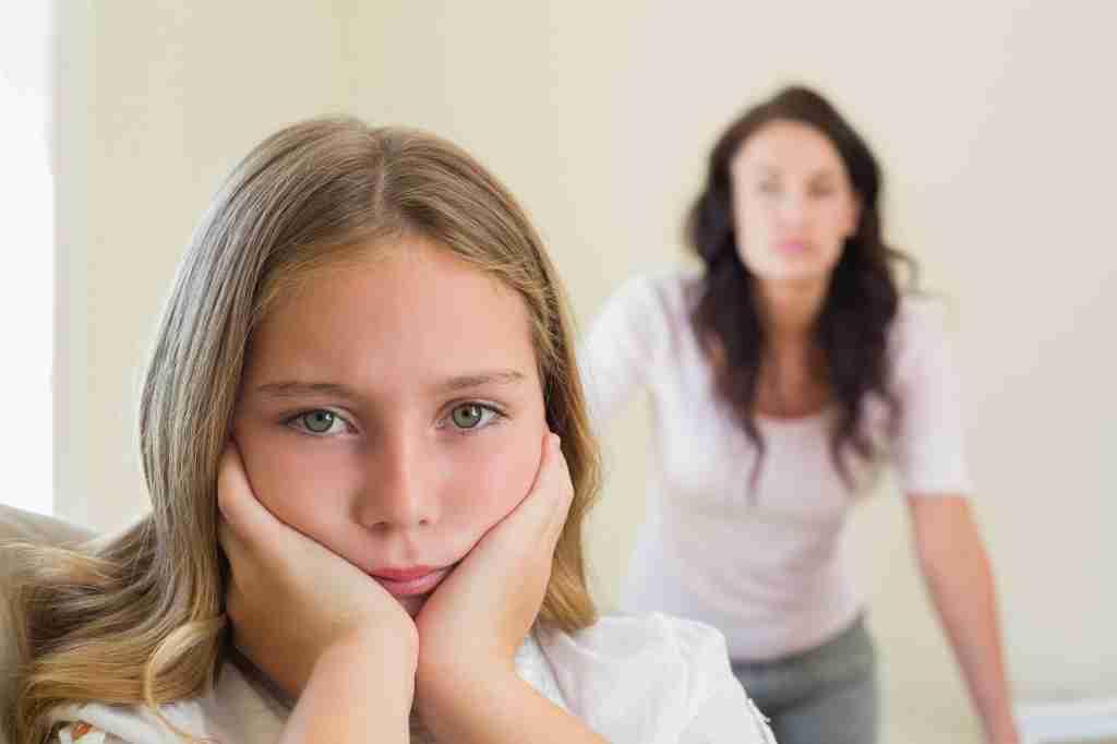 Menina insatisfeita com adulta ao fundo: exigir demais das crianças traz sérias consequências