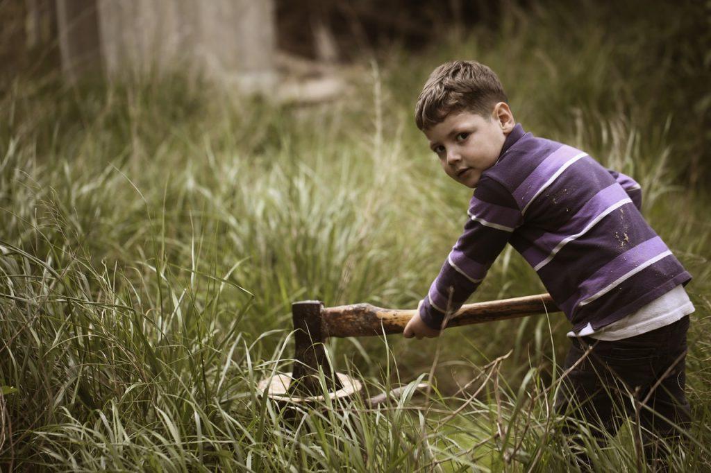 Menino cortando madeira com machado: se os filhos se comportam educamente em troca de honrarias, algo está bem errado!