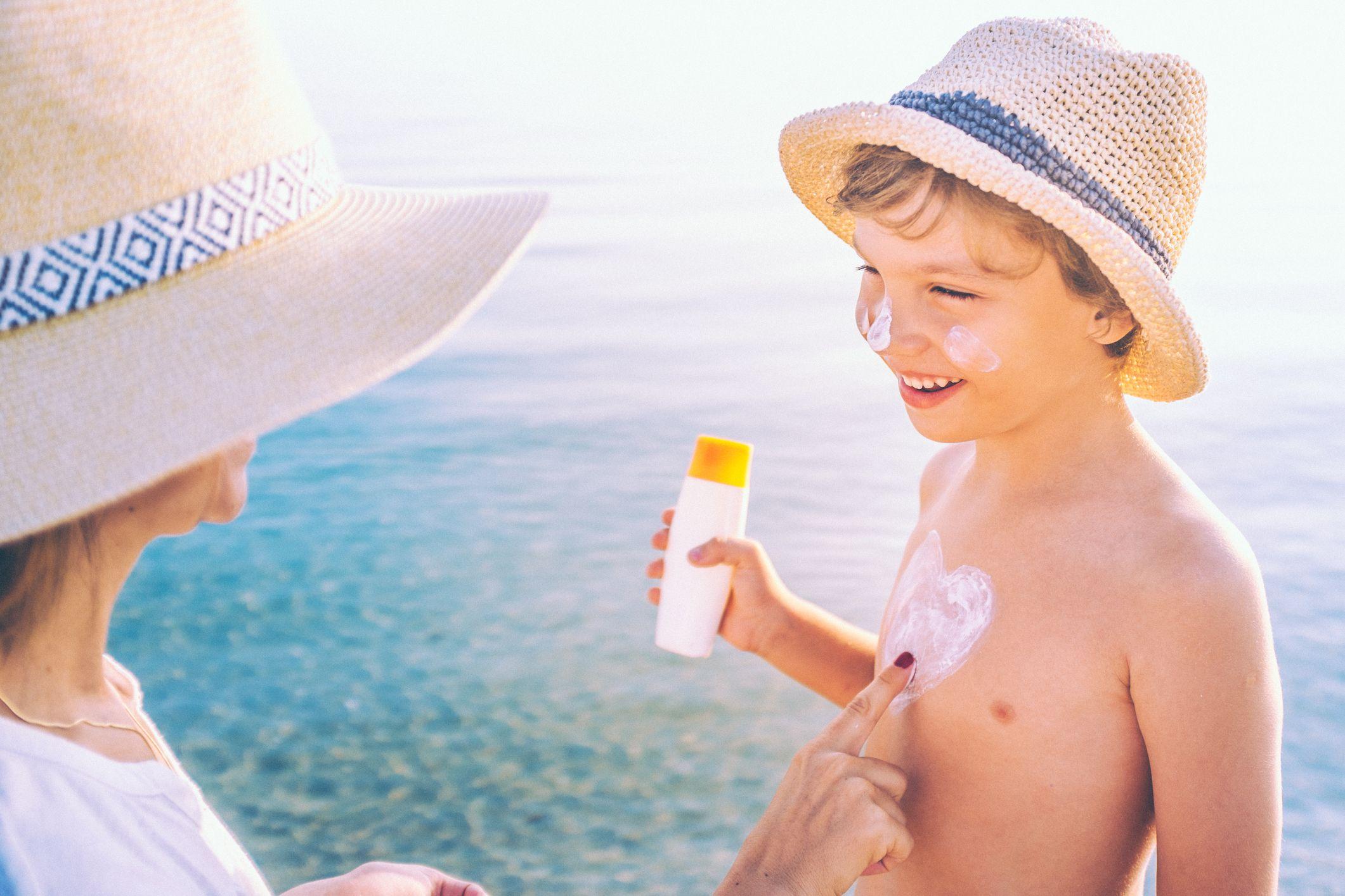 Filho recebe protetor solar da mãe: exposição ao sol dever ser feita de forma moderada