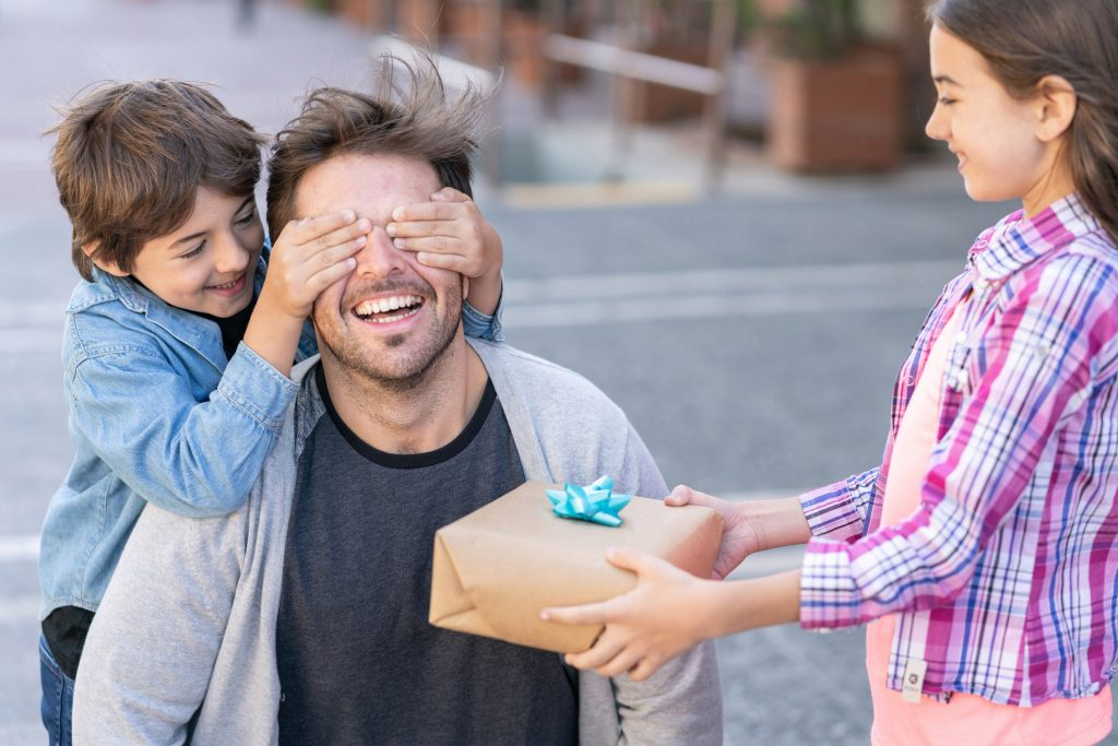 Crianças presenteiam e brincam com seu pai: tanto os filhos como seus pais têm obrigações uns com os outros