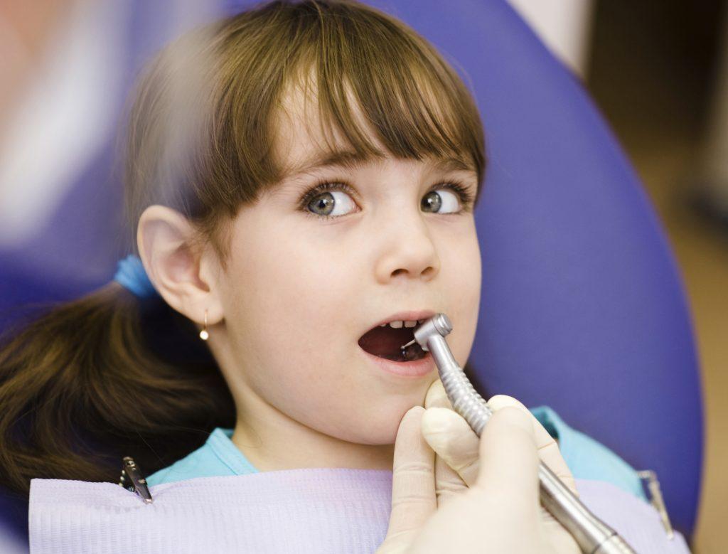 Criança na cadeira do dentista: é importante os pais ajudarem os filhos na escovação