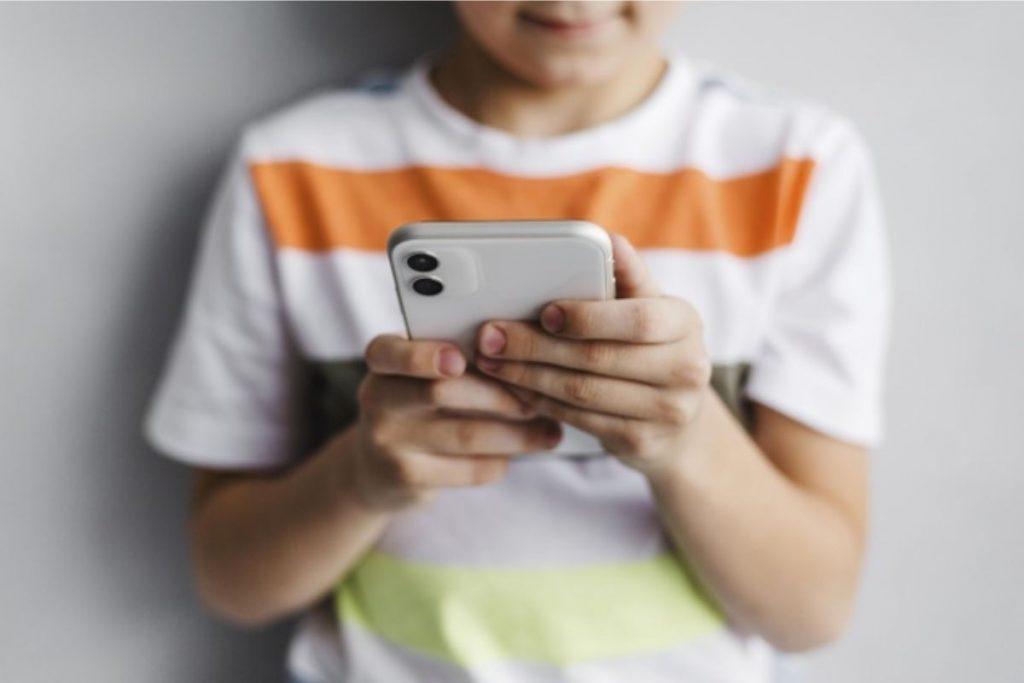 """Menino mexe em um telefone celular: TikTok também disponibiliza uma ferramenta chamada """"sincronização familiar""""; isso permite que os pais ou responsáveis incluam a própria conta com a dos filhos"""