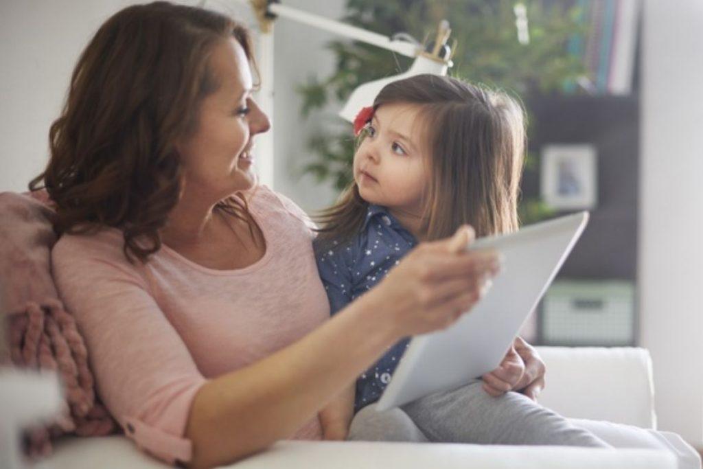 Mãe e filha conversam segurando um tablet: dialogar com cuidado é essencial para explicar ao seu filho os riscos do tiktok