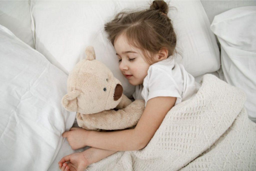 Criança dorme junto a um urso:  Existem horários ideais para as sonecas (Foto: Freepick)