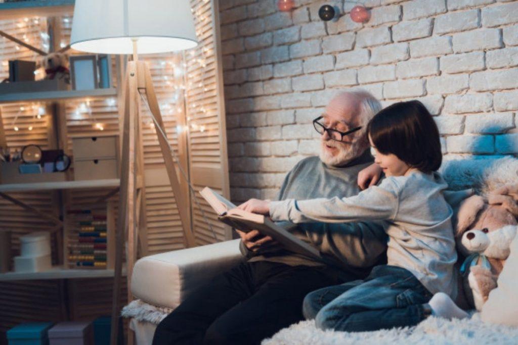Idoso e criança leem livro juntos; é importante vivenciar o carinho dos avós durante a infância (Foto: Freepik)