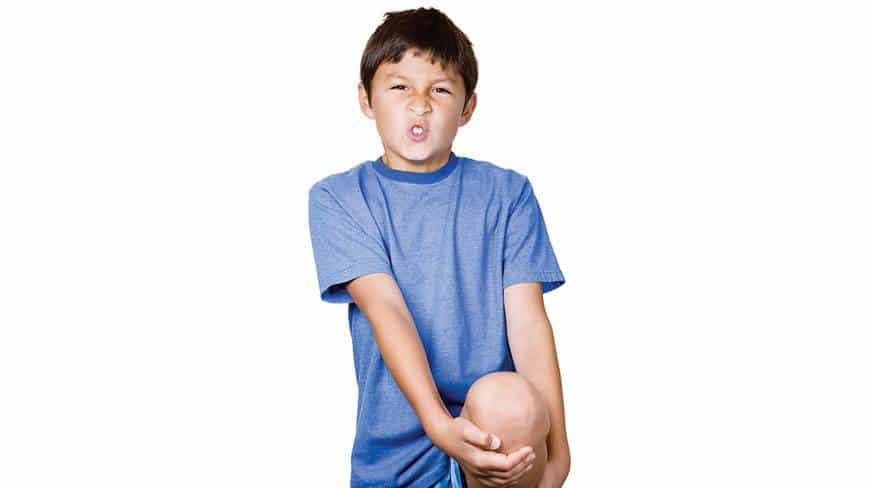 Menino com a mão no joelho: crianças podem sofrer de artrite?