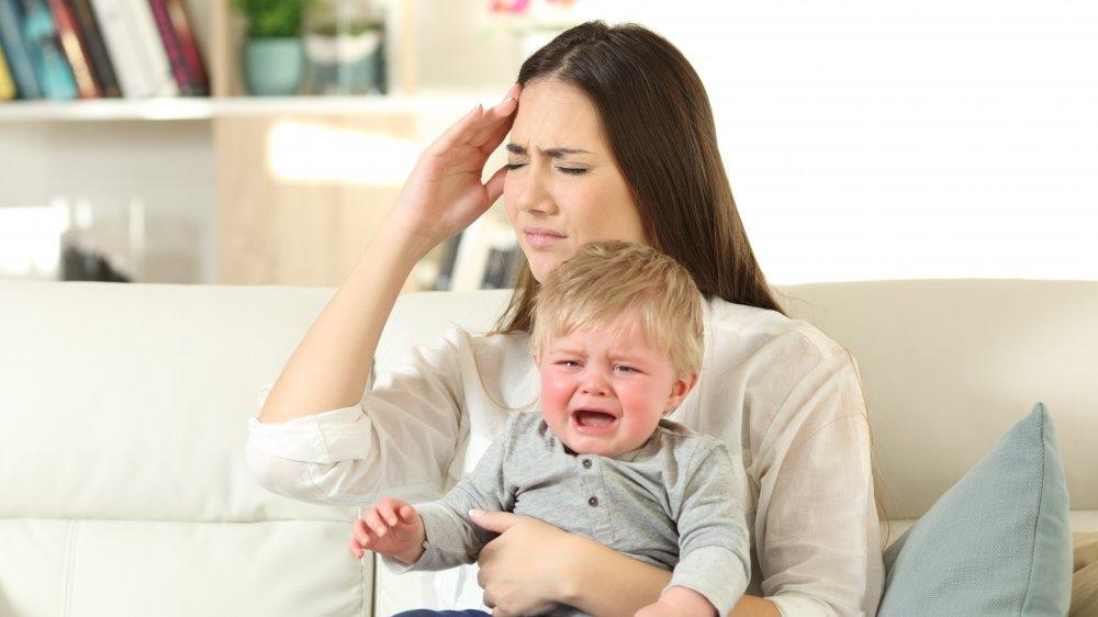 Nenê chora no colo da mãe; bebê separado da mãe: angústia do afastamento