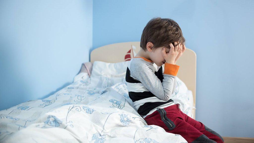 Menino triste em sua cama: pais devem ficar alertas quando a criança fizer xixi na cama acima dos 4 anos