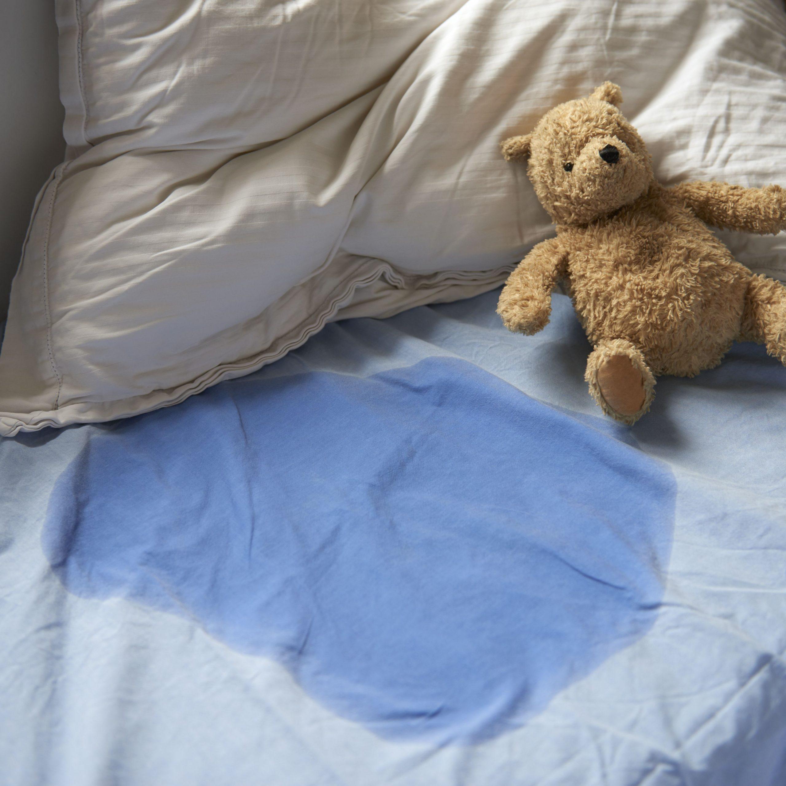 Ursinho de brinquedo ao lado de cama molhada de urina: o que fazer para conter o xixi noturno?