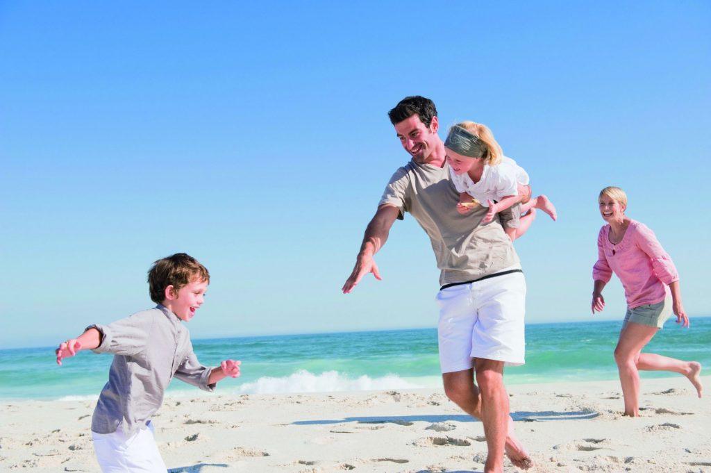 Pais e crianças na praia durante viagem: meritocracia pode ser boa para as crianças