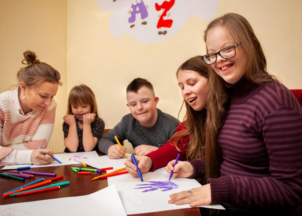 Estudantes com Down pintam em mesa de escola: pessoas com Síndrome de Down devem ser integrados normalmente à sociedade