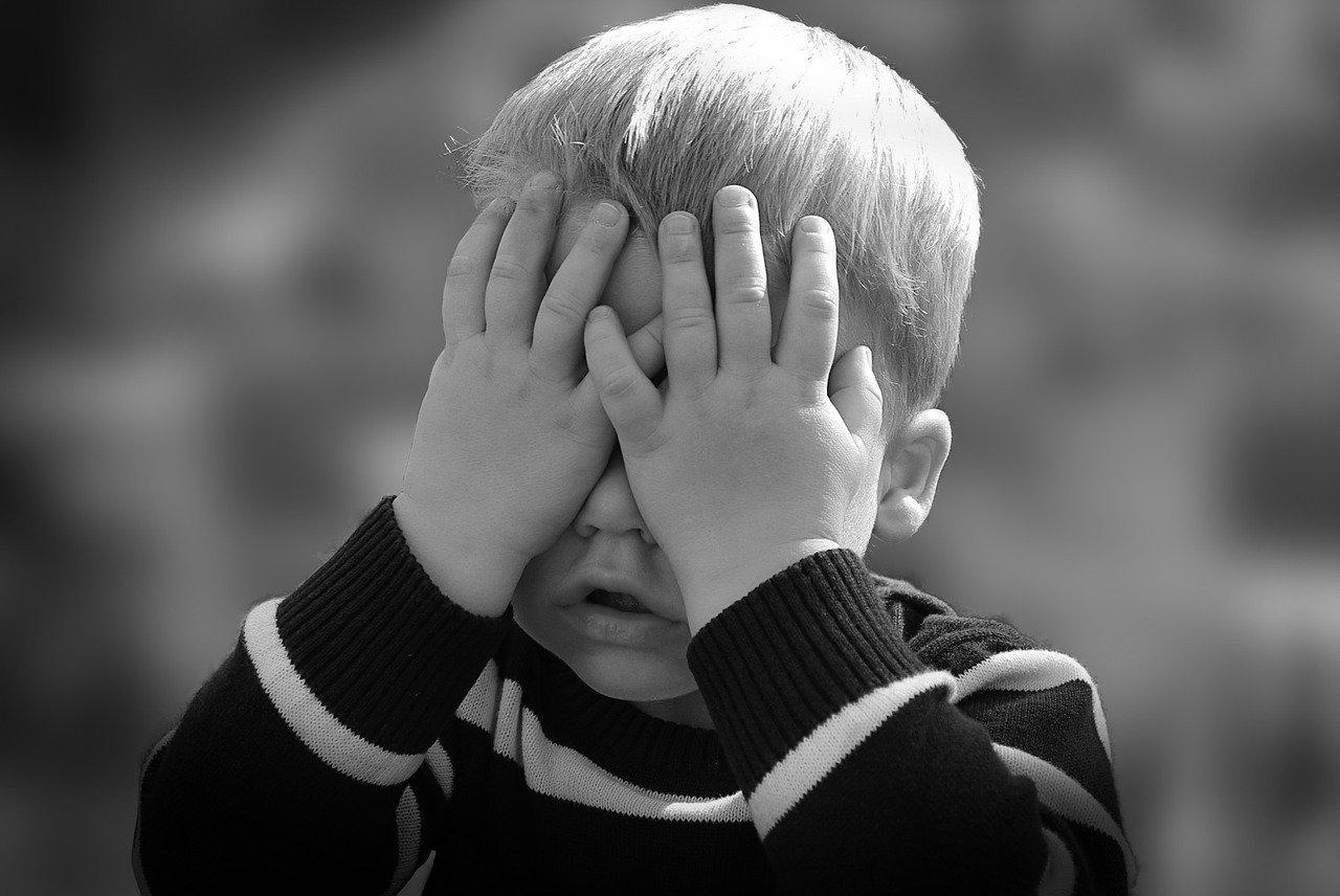 Menino triste cobre os olhos: saiba como identificar sintomas de depressão em crianças