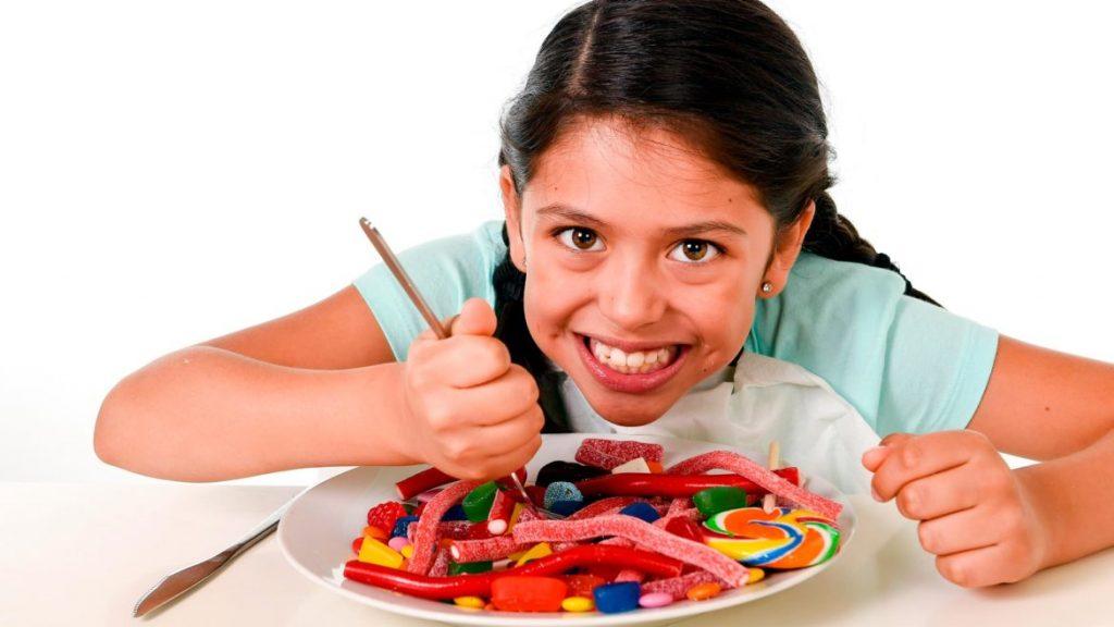 Criança comendo vários doces: bons hábitos na infância são fundamentais para evitar o colesterol
