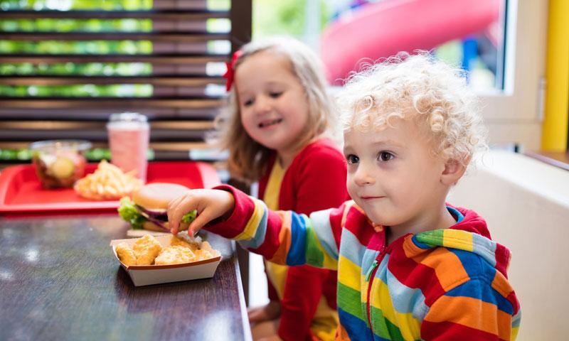 Crianças comendo frituras: problemas com o colesterol começam já na infância