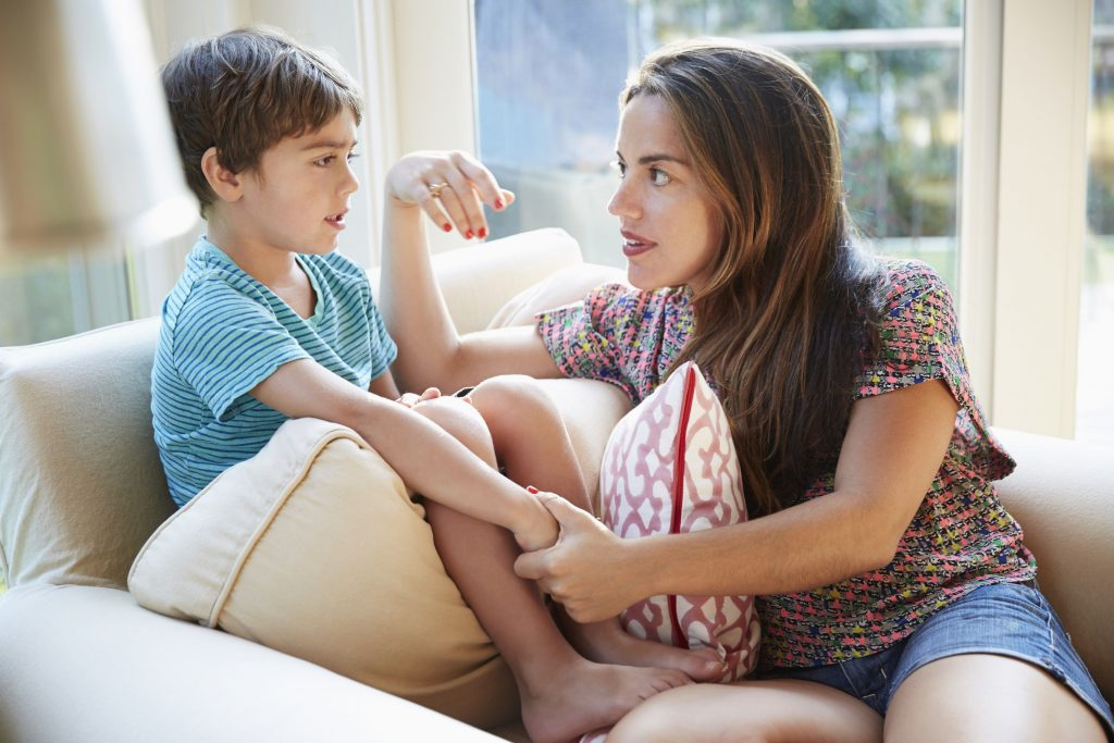Mãe segura na mão do filho durante conversa no sofá: é muito bom os pais saberem que ao ouvirem seus filhos com atenção e com interesse