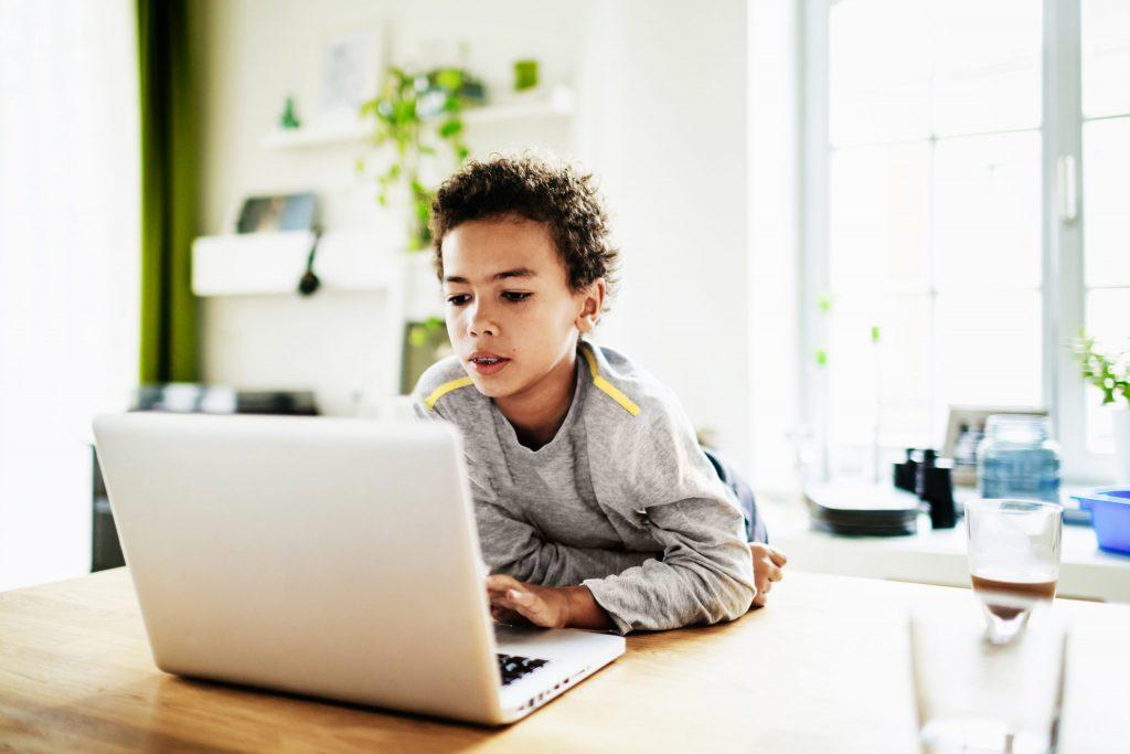 Jovem garoto usando um notebook: pais devem servir de exemplo aos seus filhos