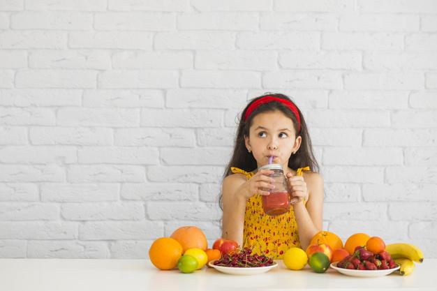 Ingerir líquidos durante as refeições: menina tomando suco