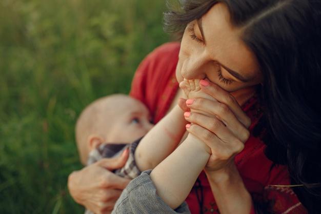 Mulher acaricia bebê enquanto o amamenta