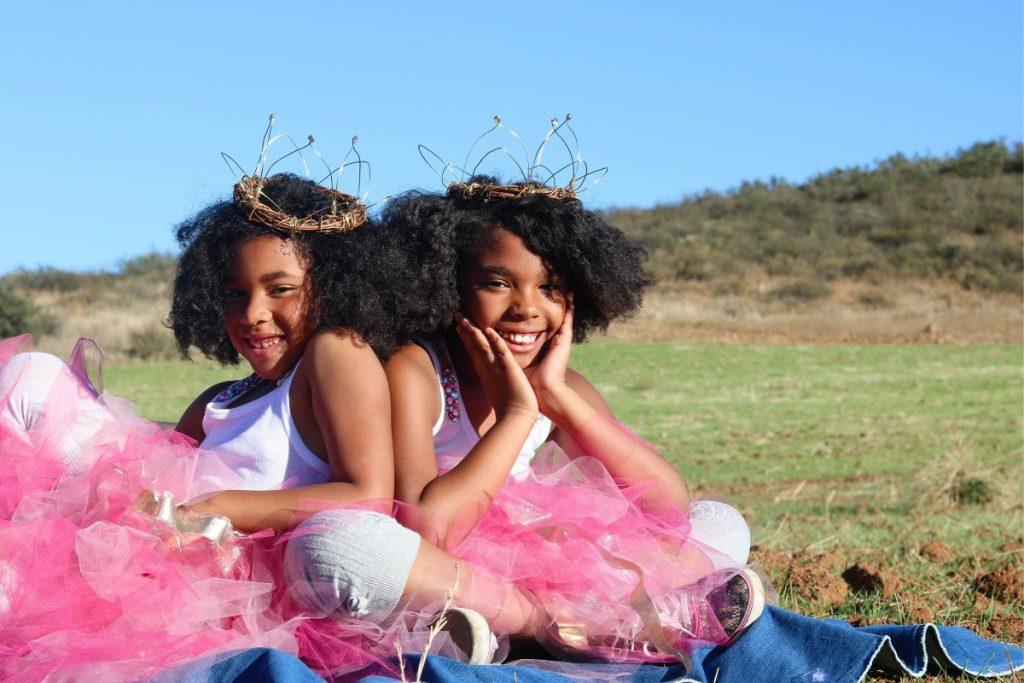 Irmãs gêmeas sorriem em campo: gêmeos criam laços ainda na barriga da mãe. Foto Unplash